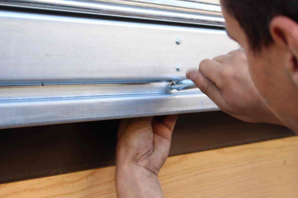Key Rapid cerrajero que está ajustando una persiana